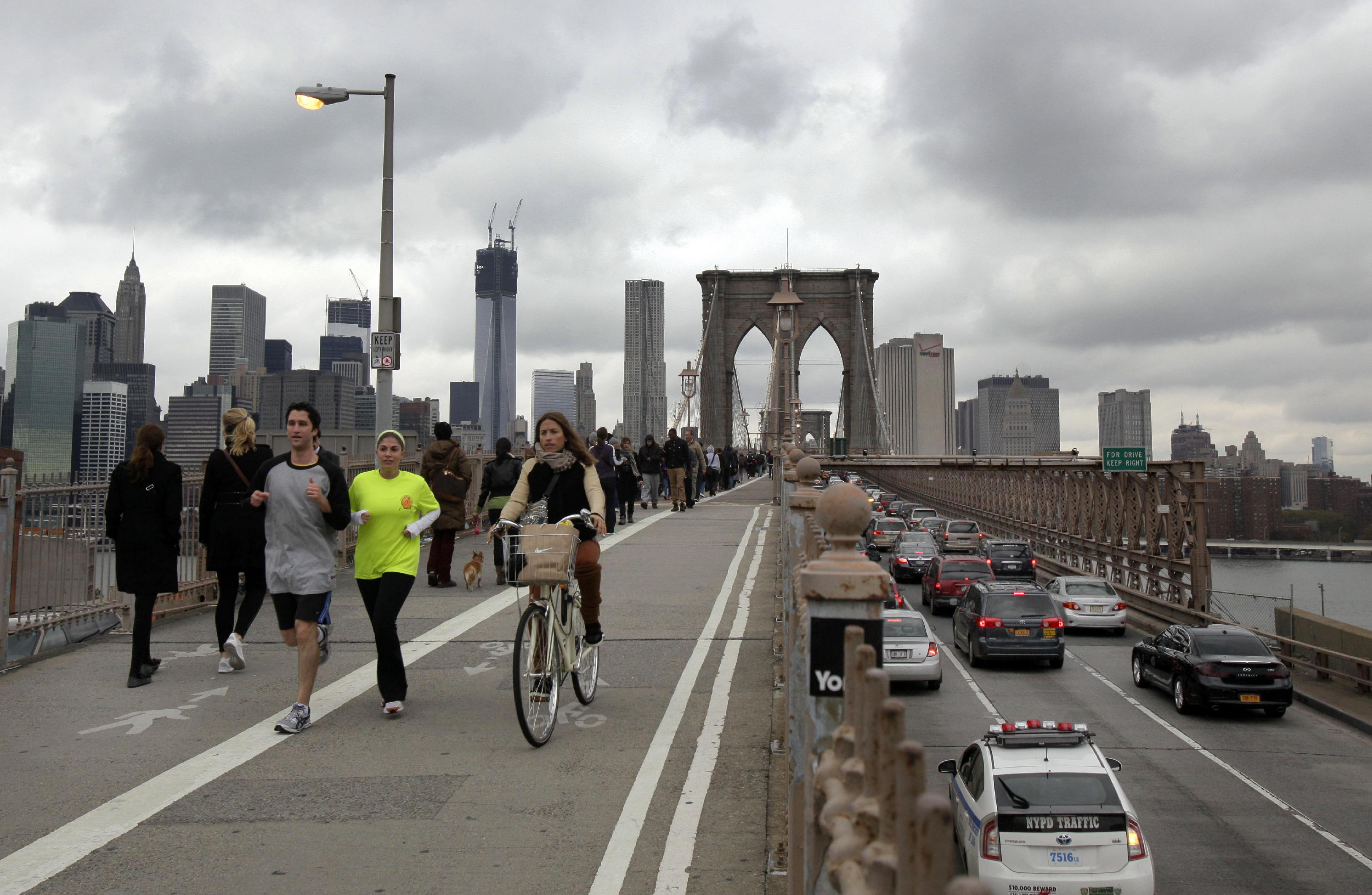 Commuters cross New York's Brooklyn Bridge.— AP Photo