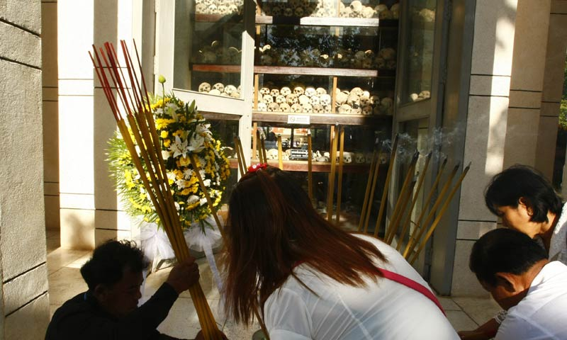 """In this photo taken, May 20, 2013, Cambodians  place burning incense sticks and offer prayers at a memorial charnel housing skulls of unidentified victims of the Khmer Rouge in Choeung Ek """"Killing Field"""" in Phnom Penh, Cambodia. - AP Photo"""