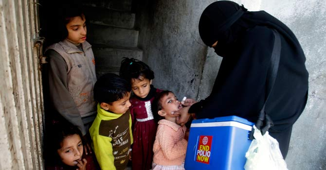 A Pakistani health worker gives polio vaccine to a childPakistan. -AP Photo