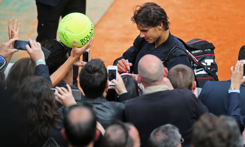 Spain's Rafael Nadal signs autographs after defeating Germany's Daniel Brands in their first round match. Nadal won in four sets 4-6, 7-6, 6-4, 6-3. —AP Photo