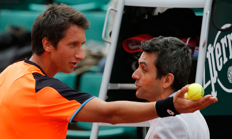Ukraine's Sergiy Stakhovsky, left, argues the decision of the umpire to call the ball in, in his first round match against Richard Gasquet of France. Stakhovsky later took a picture of the mark of the ball on the clay court with his smart phone. —AP Photo