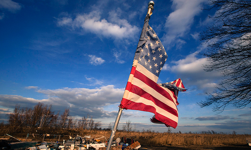 "A tattered US flag flies over the foundation of a home destroyed by the storm surge of super storm Sandy in the Staten Island borough neighborhood of Oakwood in New York in this November 28, 2012 file photo. The US Flag Code, part of federal law governing display of the flag, requires that flags be ""destroyed in a dignified way, preferably by burning."" — Reuters Photo"
