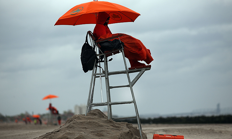 Life guard Paul Shmidt tries to stay warm on a chilly afternoon at the beach at Coney Island on the first weekend of city beaches re-opening to the public on May 25, 2013 in the Brooklyn borough of New York City. While warmer weather and sunny skies are expected for the remainder of the holiday weekend, cool temperatures and rain kept area beaches largely empty.  — AFP Photo