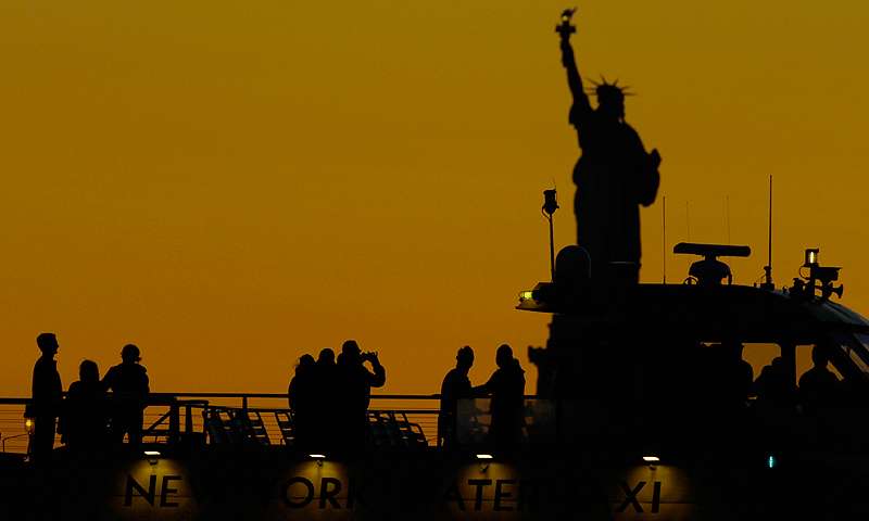 People on a water taxi pass by the Statue of Liberty as the sun sets in New York, May 26, 2013. The statue and Liberty Island will reopen to the public on July 4 after having been damaged by Hurricane Sandy last year. — Reuters Photo