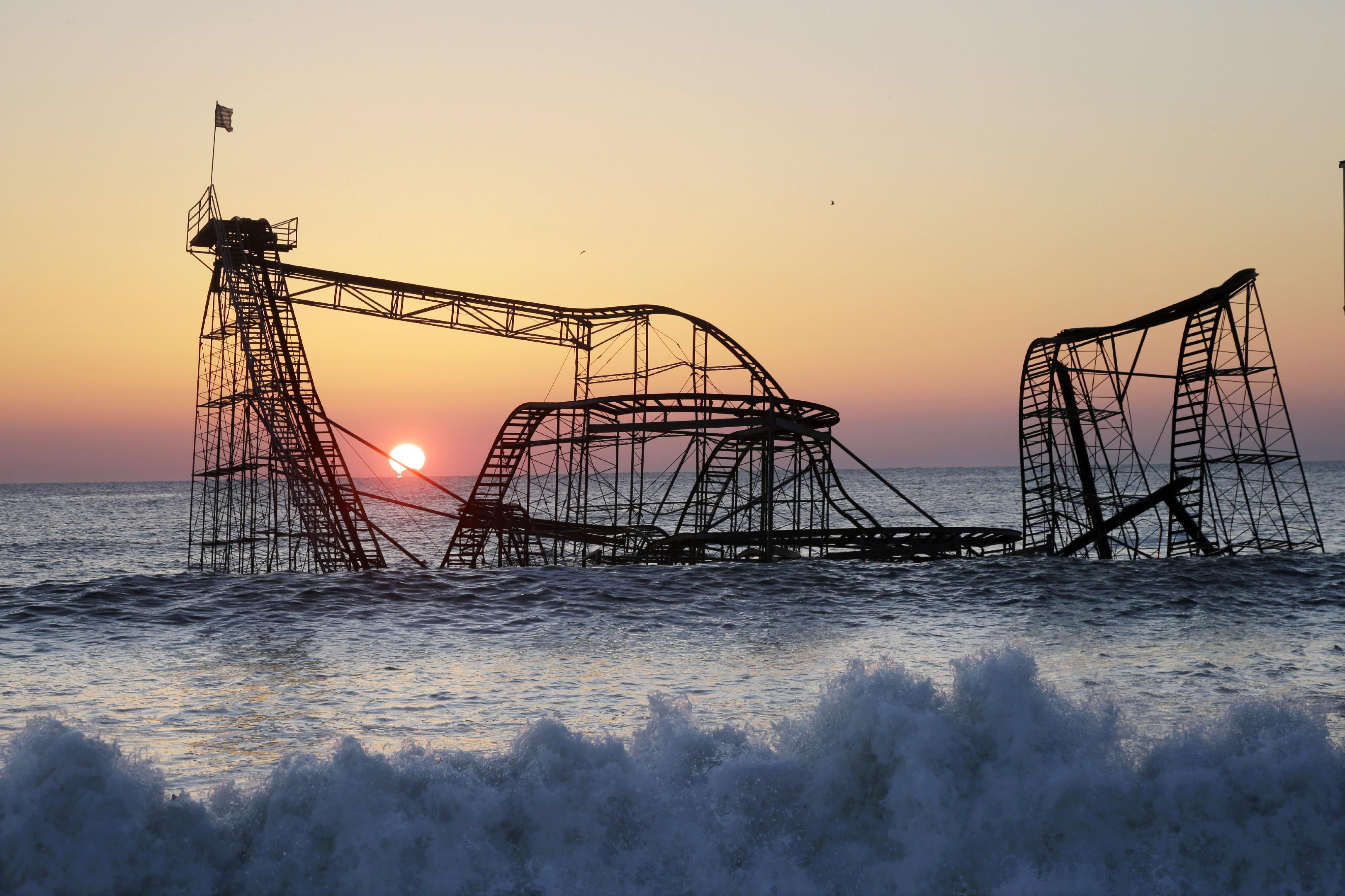 In a Feb. 25, 2013 file photo, the sun rises in Seaside Heights, N.J., behind the Jet Star Roller Coaster which has been sitting in the ocean after part of the Casino Pier was destroyed during Superstorm Sandy. Work is expected to start Tuesday afternoon, May 14, 2013 to remove the Jet Star coaster from the surf in Seaside Heights. — AP Photo