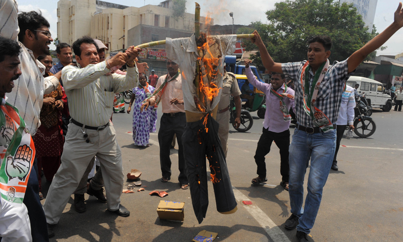 Congress workers and supporters burn an effigy of 'Naxalism' as they protest against the attack by Maoists on Congress party members in the central state of Chhattisgarh, in Ahmedabad on May 27, 2013. A heavily-armed gang of nearly 300 Maoist rebels killed at least 23 people in an attack on a convoy of local Congress party leaders and supporters in central India, police said Sunday. —  AFP PHOTO
