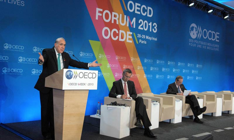 OECD Secretary General Angel Gurria (L) talks as Norway Prime Minister Jens Stoltenberg (C) and OECD Chief Economist Pier Carlo Padoan listen during the presentation of the Economic Outlook during the OECD Week at the OECD headquarters in Paris on May 29, 2013. - AFP Photo