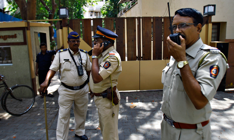 Police men speak on a wireless radio as they stand outside a complex that houses the home of Bollywood actress Jiah Khan in Mumbai, India, Tuesday, June 4, 2013. — AP Photo