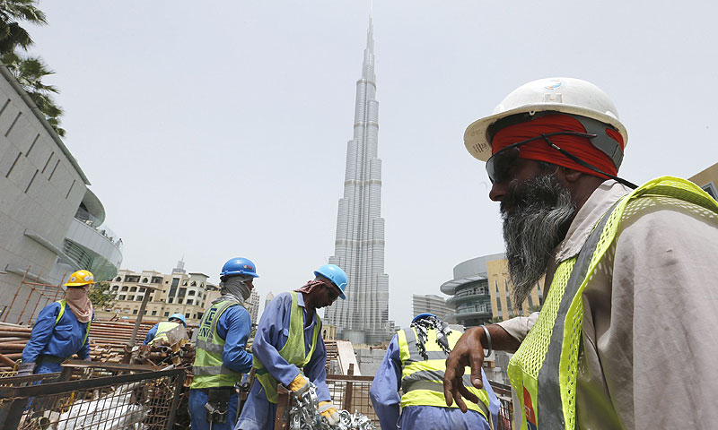 Labourers work near the Burj Khalifa, the tallest tower in the world. — Photo by Reuters