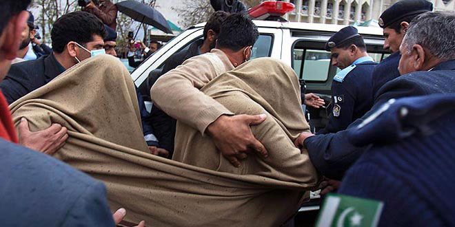 Photo from February 2012 shows a 'missing person' being ushered away by authorities in Islamabad after  being presented in the Supreme Court.—File Photo