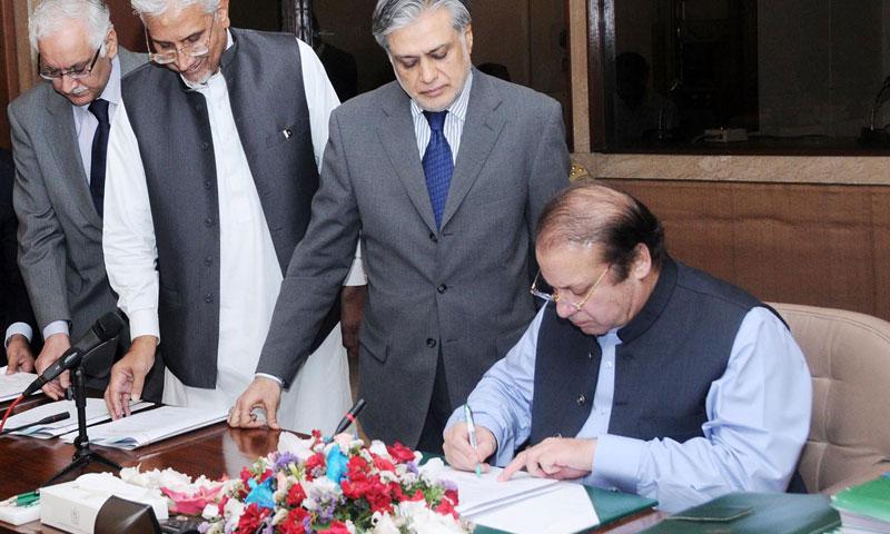 کابینہ کی جانب سے بجٹ 14-2013 کی منظوری دیے جانے کے بعد سابق وزیراعظم بجٹ دستاویر پر دستخط کر رہے ہیں۔