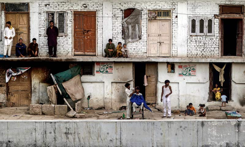 During a power cut Pakistanis gather outside to escape the heat trapped in their homes while a street barber gives a customer a haircut in Rawalpindi. -AP Photo