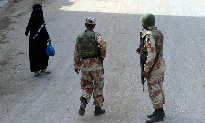 Rangers personnel stand guard at an area cordoned off during a house-to-house search operation in Karachi Orangi Town. — Photo by AFP