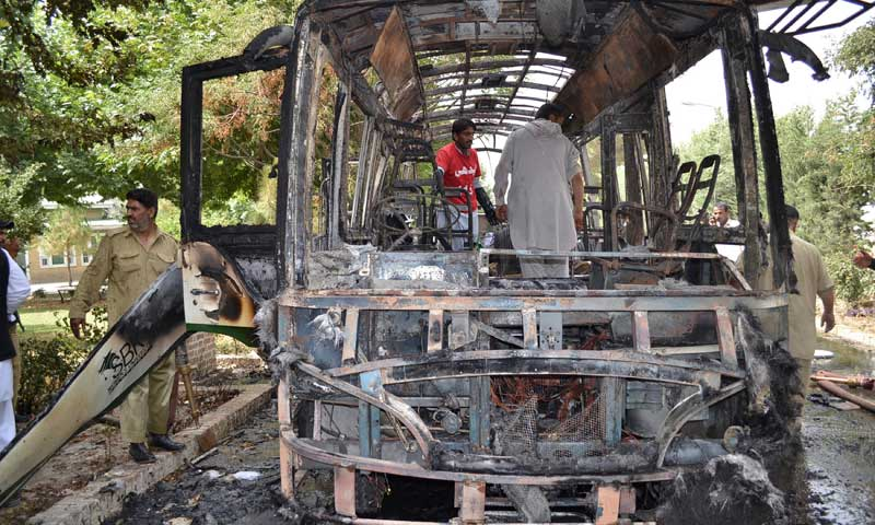 Volunteers collect body parts of victims of a bomb blast from the wreckage of a bus in Quetta, June 15, 2013. — Photo by AP