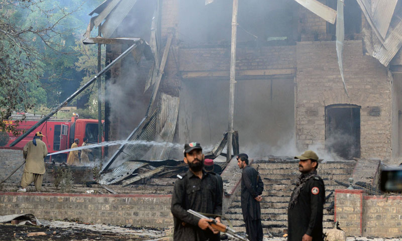 Pakistani security personnel look on as firefighters extinguish a blaze which gutted a historical building in Ziarat, 80 kilometres southeast of Quetta, on June 15, 2013. - Photo by AFP