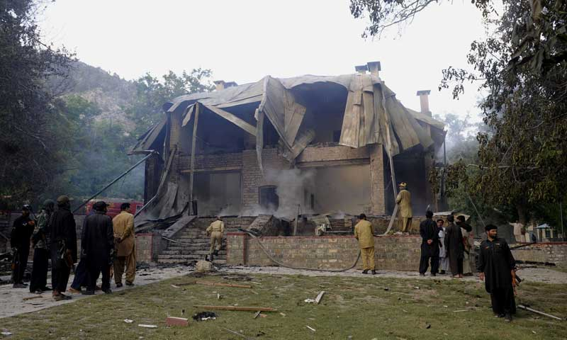 Security personnel gather as firefighters extinguish a blaze which gutted Jinnah's residency in Ziarat, 80 kilometres southeast of Quetta, June 15, 2013. — Photo by AFP