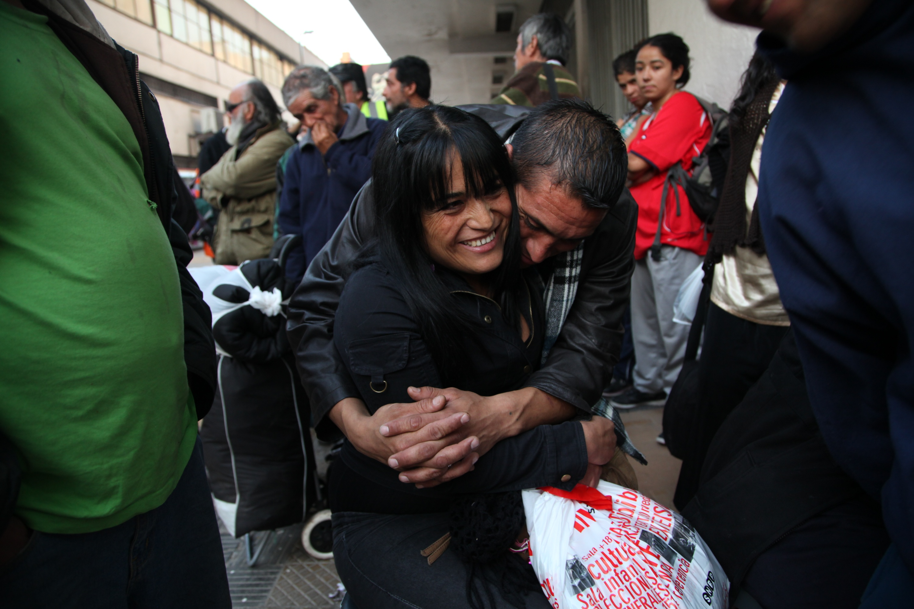 Jonathan Fuentes hugs his girlfriend Vivian Alvarez as they wait for the shelter to open for the evening at the indoor stadium Estadio Victor Jara