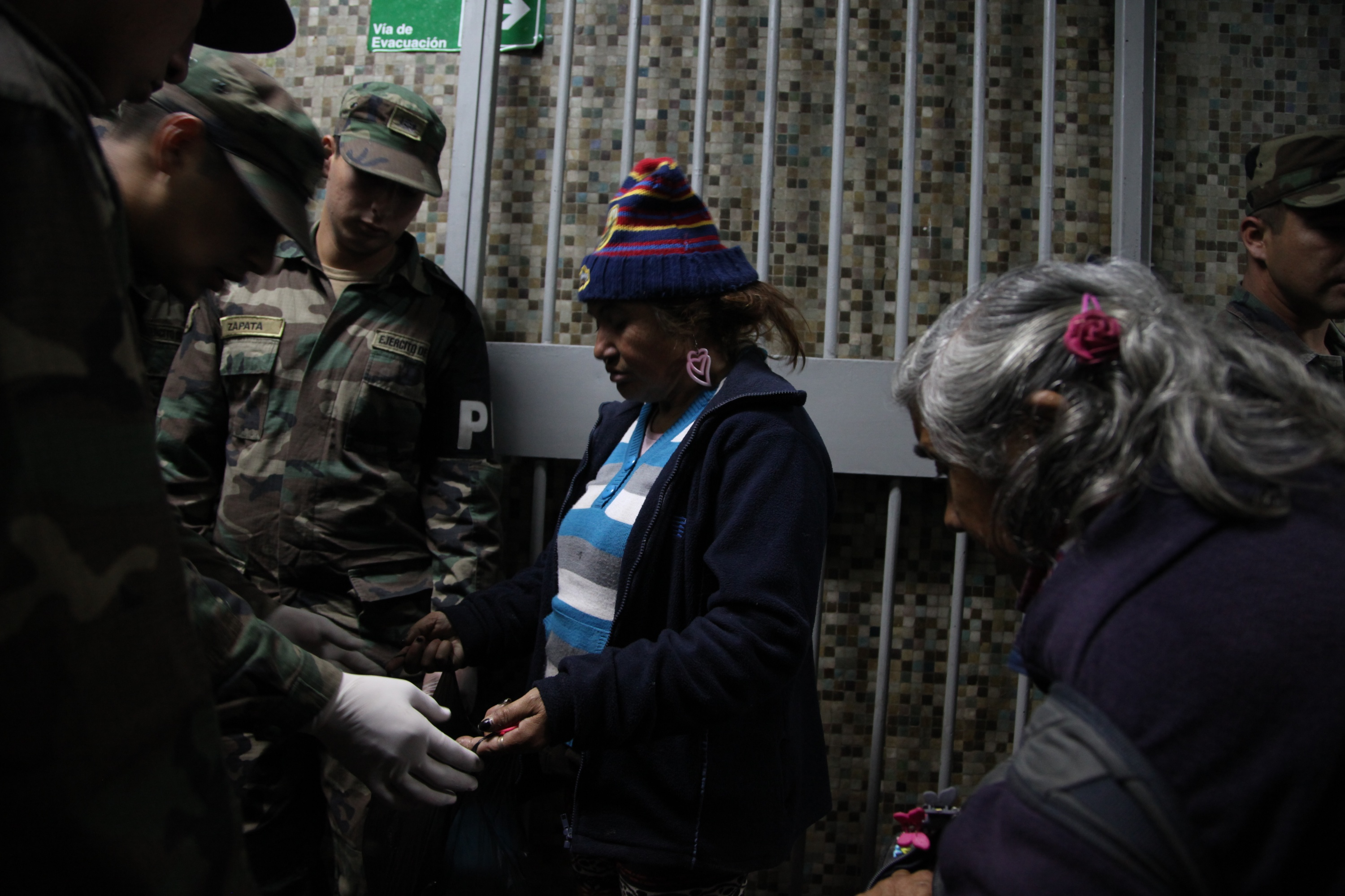 A woman opens her bag for soldiers to search through before entering a homeless shelter at the indoor stadium Estadio Victor Jara.
