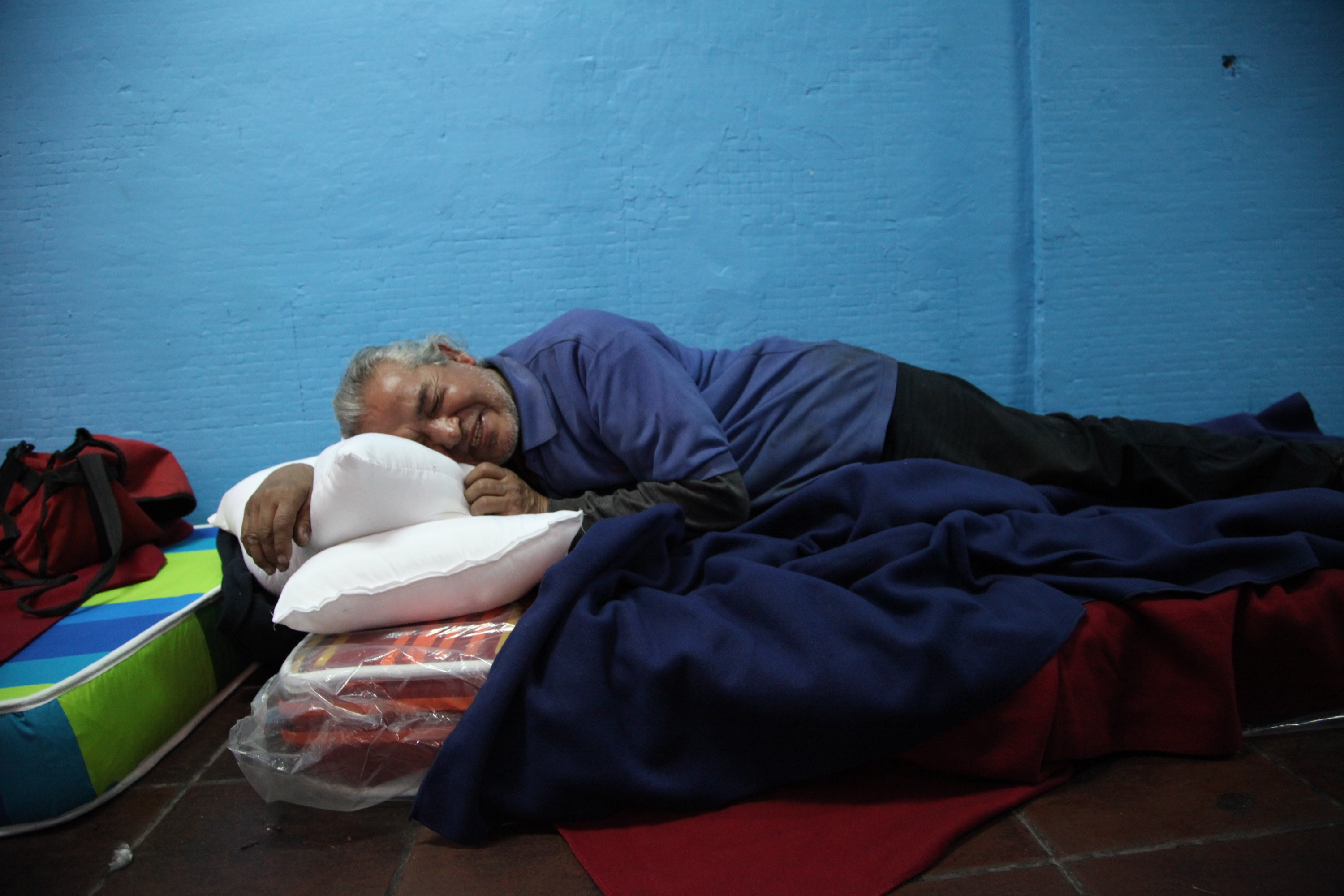 Armando Patricio Galleguillos Luna, 63, lies on a mattress in the designated area for people who have been using a substance, before they can access the rest of the shelter at the indoor stadium Estadio Victor Jara in Santiago, Chile.