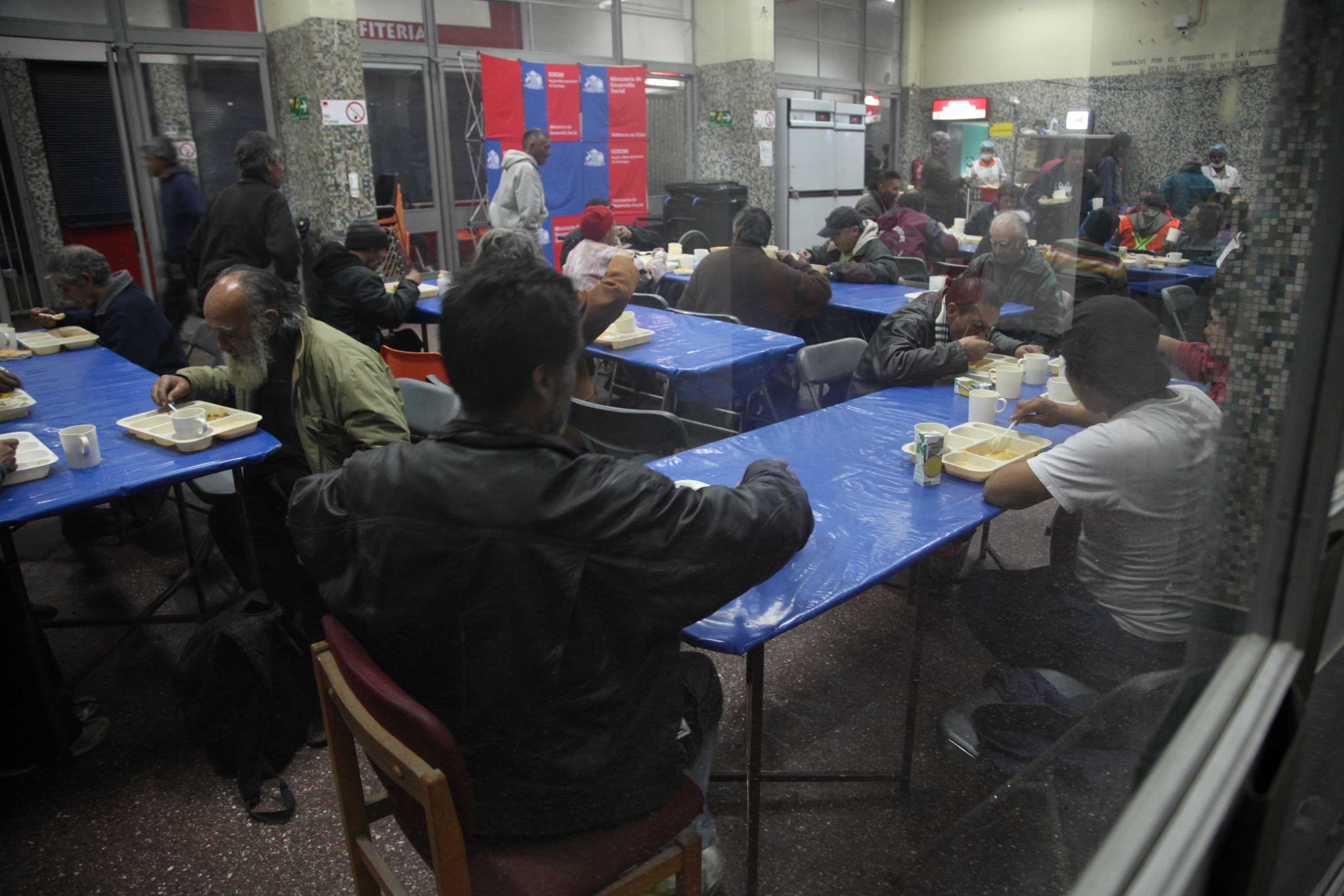 People eat a hot dinner at the indoor stadium Estadio Victor Jara.