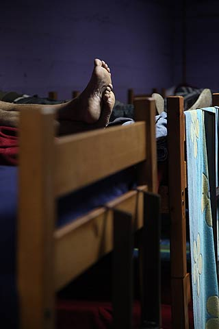 Men relax on their bunk beds inside the heated shelter at the indoor stadium Estadio Victor Jara.