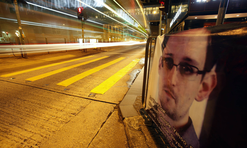A bus passes by a poster of Edward Snowden, a former contractor at the National Security Agency (NSA), displayed by his supporters at Hong Kong's financial Central district during the midnight hours of June 18, 2013. - Reuters Photo