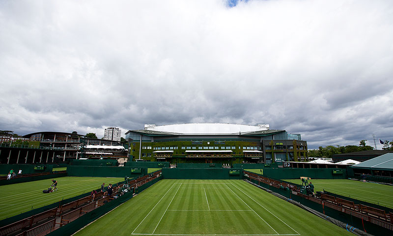 Groundsmen make final preparations on the outside courts backdropped by Centre Court, for the start of the Wimbledon tennis championships in London. -Photo by AP