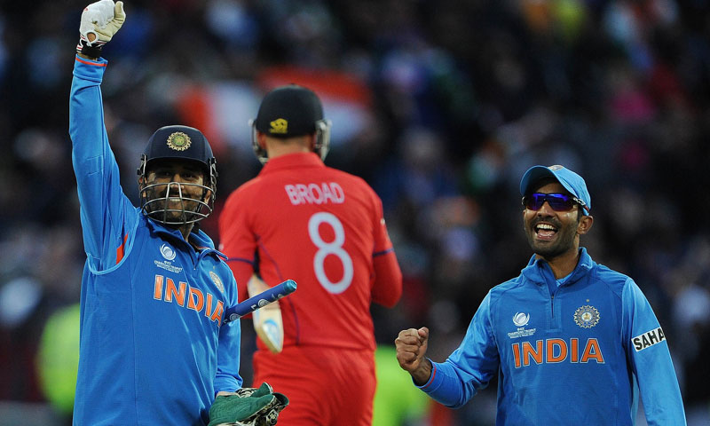 Indian captain Mahendra Sing Dhoni (L) and teammate Dinesh Karthik (R) celebrate victory. - Photo by AFP