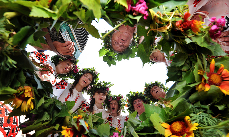"Belarussian women wearing traditional clothes and holding flowers sing in the village of Plastok, some 175 kms south of Minsk, as part of festivities surrounding the Orthodox ""Trinity's Day"" holiday.—Photo by AFP"