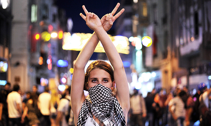 An anti goverment protester flashes a victory sign during the clashes between protestors and riot police on Taksim square in Istanbul.  Turkish police used water cannon today to disperse thousands of demonstrators who had gathered anew in Istanbul's Taksim Square, calling for the resignation of Prime Minister Recep Tayyip Erdogan.—Photo by AFP