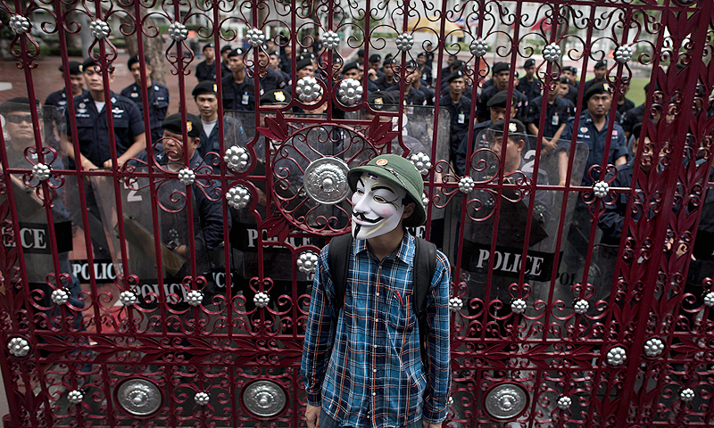 A protester wearing a Guy Fawkes mask, stand in front of a gate secured by Thai police officers as he and thousands of protesters gather in Bangkok's shopping district. Thousands of people marched through central Bangkok to protest against the former prime minister Thaksin Shinawatra and the current government led by his sister Thai Prime minister Yingluck Shinawatra.—Photo by AFP