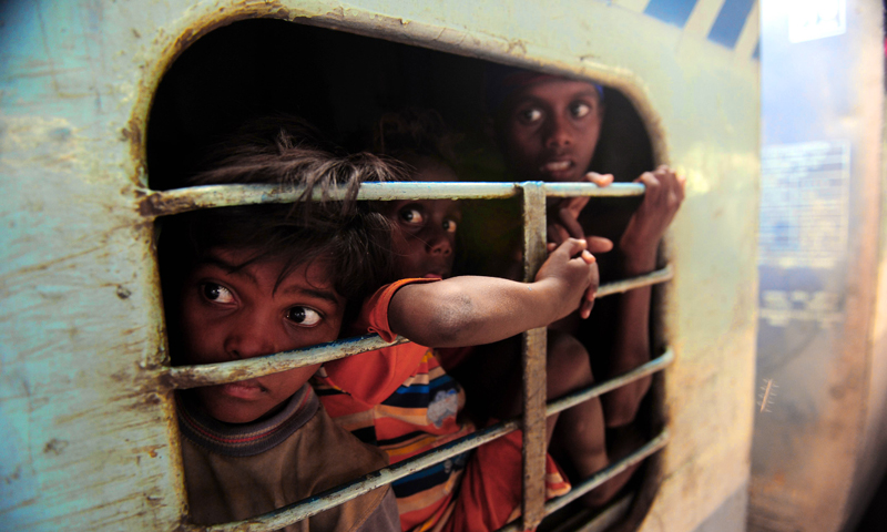 Young Indian commuters sit inside a crowded train compartment at Allahabad junction in Allahabad.—Photo by AFP