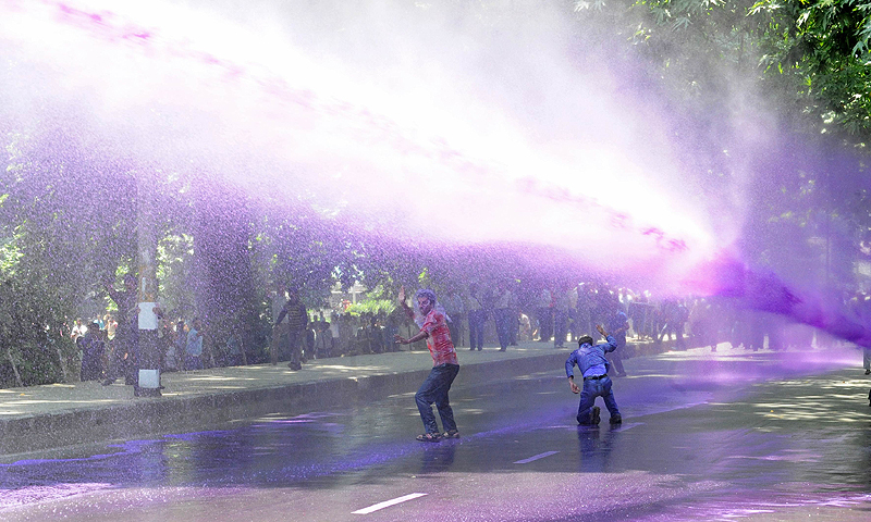 Kashmiri government employees demonstrate as riot police spray them with a purple-dyed water cannon in Srinagar.  Dozens of government employees were arrested as they tried to stage a protest march in Srinagar demanding an regularisation of contractual jobs and an increase in salary.—Photo by AFP
