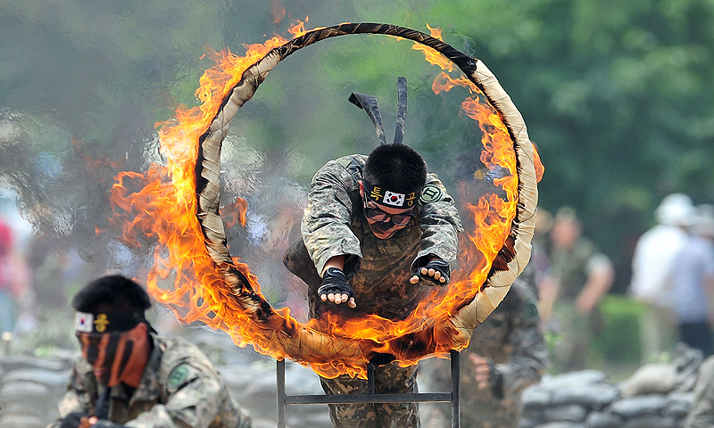 A South Korean soldier jumps through a flaming ring as others perform martial arts during a ceremony for a re-enactment of the battle of Chuncheon at the beginning of the 1950-53 Korean War, to mark its 63th anniversary in Chuncheon, South Korea. The Korean peninsula is the world's last Cold War frontier as Stalinist North Korea and pro-Western South Korea have been technically at war since the 1950-53 conflict.—Photo by AFP