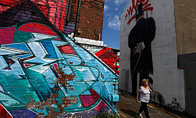 "A man pushes his bicycle past murals painted on the side of a building in Blackpool, northern England June 18, 2013. The mural is part of the ""Sand, Sea and Spray"" outdoor art festival, which has seen 40 urban artists from around the world paint murals on buildings across the town centre. — Reuters Photo"