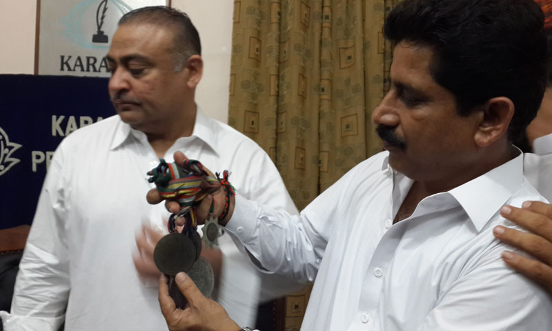 President Pakistan People's Party Karachi division, Abdul Qadir Patel, looks sideways as provincial lawmaker Jawed Nagori shows medals won by Shoaib 'Boxer' during national boxing tournaments.—Photo by author