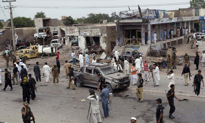 Pakistani security officials and media person gather at the site of car bombing on the outskirts of Peshawar, Pakistan, Sunday, June 2013.   — Photo by AP