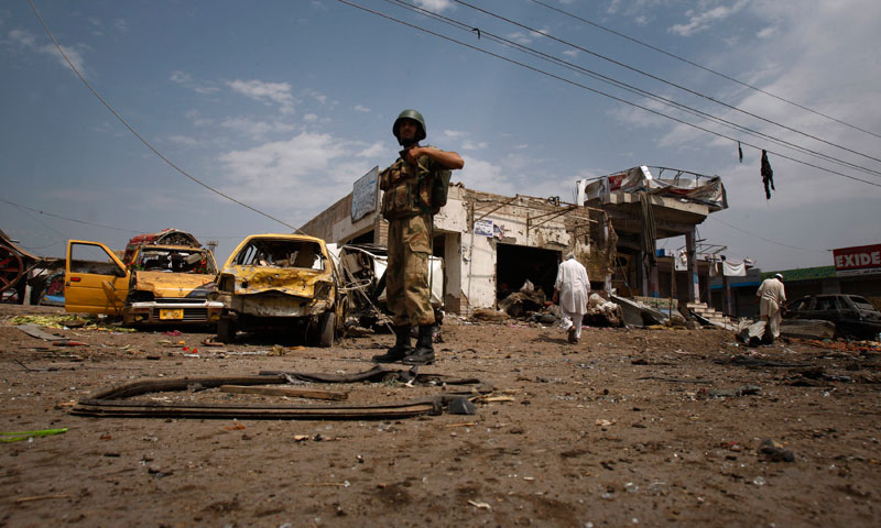 A Pakistan army soldier examines the site of a car bombing on the outskirts of Peshawar, Pakistan, Sunday, June 2013. — Photo by AP