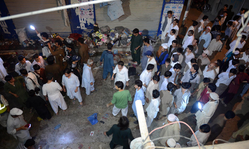 Pakistani rescuers and residents gather at the suicide attack site in Quetta on June 30, 2013. — Photo by AFP