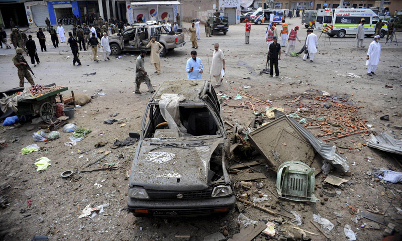 Pakistani security personnel and bystanders are pictured at the site of a bomb attack in Badaber, on the outskirts of Peshawar, on June 30, 2013. — Photo by AFP