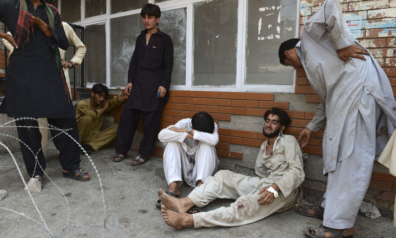 Relatives mourn the death of loved ones, killed during a bomb attack in nearby Badaber, outside a hospital in Peshawar on June 30, 2013. — Photo by AFP