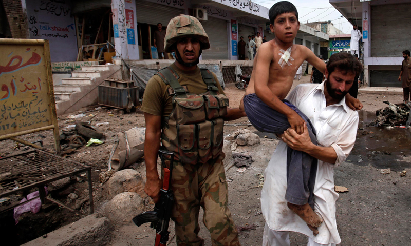 A security official carries a boy who was injured in a bomb attack from the site in the outskirts of Peshawar June 30, 2013. — Reuters Photo.