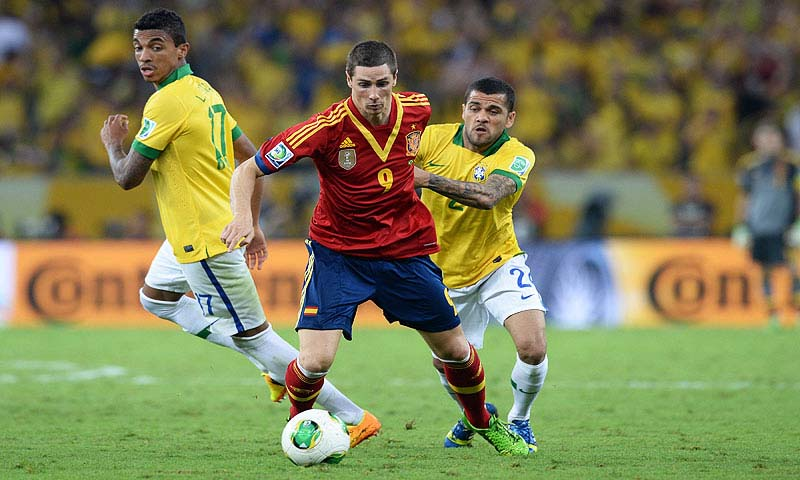 Spain's forward Fernando Torres (C) vies with Brazil's defender Dani Alves (R) - Photo by AFP