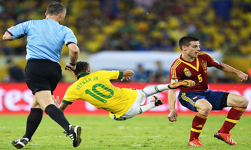 Brazil's forward Neymar (C) falls next to Spain's defender Cesar Azpilicueta (R) and referee Bjorn Kuipers - Photo by AFP