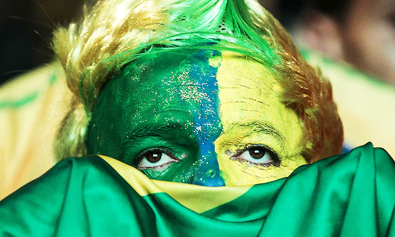 A Brazillian fan watches the match on a giant screen - Photo by AFP