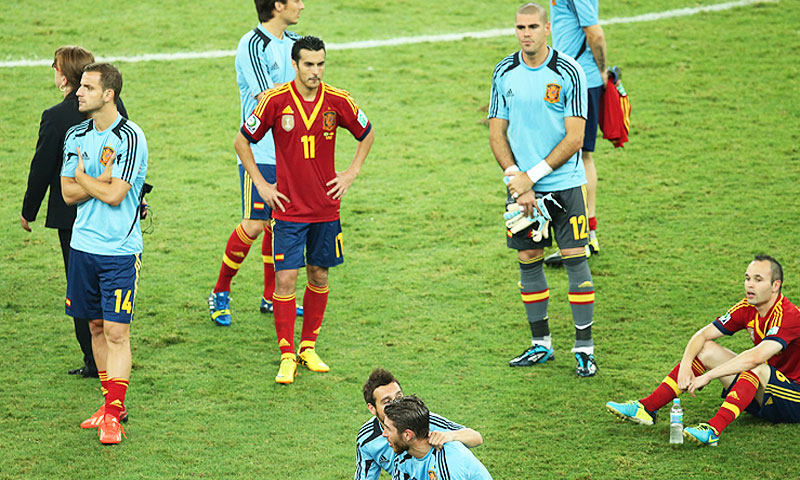 Spanish players sit dejected on the pitch after losing - Photo by AP