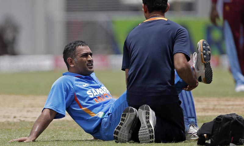 India's captain Mahendra Singh Dhoni, left, is tended by the team physiotherapist after injuring his leg during the Tri-Nation Series cricket match against the West Indies in Kingston, Jamaica, Sunday, June 30, 2013. The Board of Control for Cricket in India (BCCI) announced on Monday that Dhoni has been ruled out of the ongoing Tri-Nation Series due to a hamstring injury and he will be replaced by Ambati Rayudu. — Photo by AP