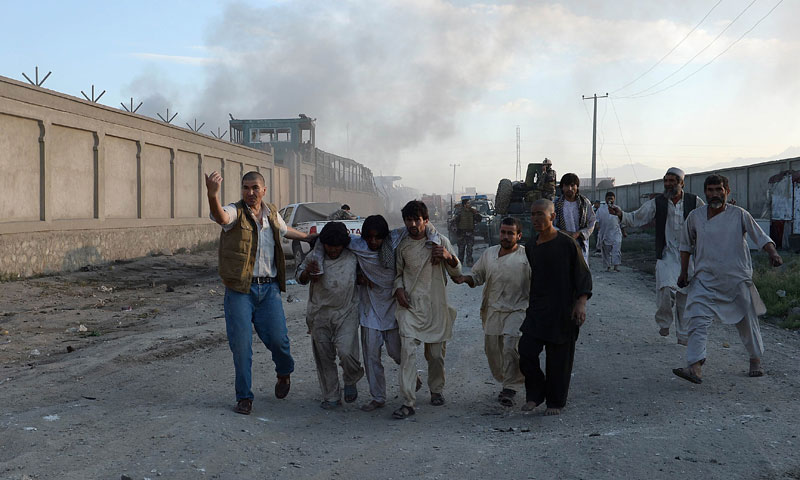 Afghan men carry a wounded man as smoke rises from the entrance gate of at a foreign logistics company at the site of a suicide attack in Kabul on July 2, 2013. — Photo by AFP