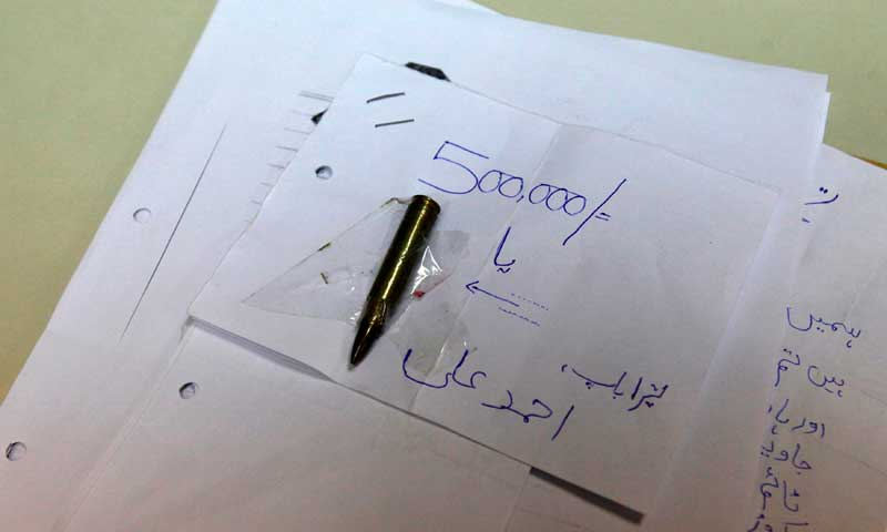 A civil society group, the Citizens Police Liaison Committee (CPLC), displays one of several extortion demands handed over to them by businessmen based in Karachi, June 14, 2013. — Photo by Reuters