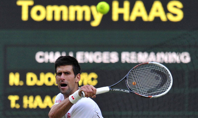 Serbia's Novak Djokovic hits a return against Germany's Tommy Haas during their fourth round men's singles match on day seven of the 2013 Wimbledon tennis tournament.